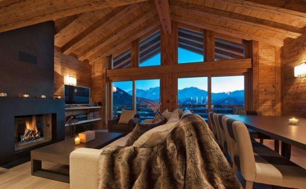 Wohnzimmer Chalet Holz Kaminofen Pelz Tagesdecken