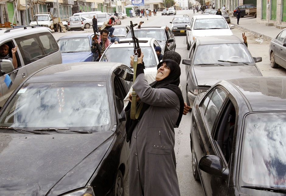 A woman rebel fighter supporter shoots an AK-47 rifle as she reacts to the news of the withdrawal of Libyan leader Muammar Gaddafi's forces from Benghazi March 19, 2011. REUTERS/Goran Tomasevic