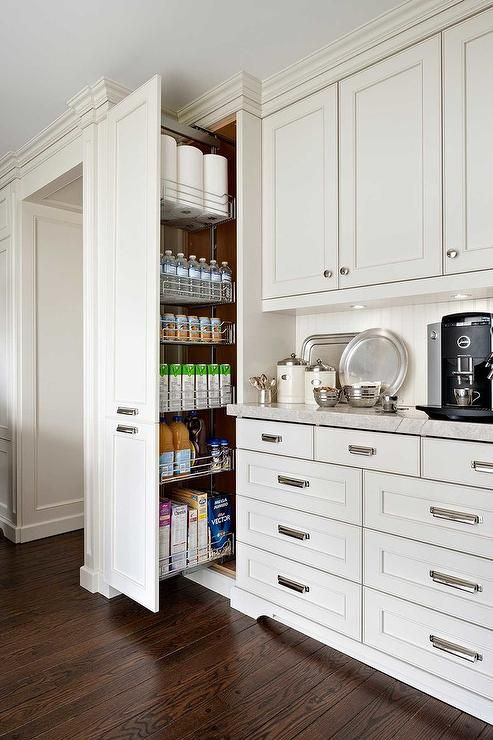 Pull-out kitchen cabinet is installed in this white kitchen with ...