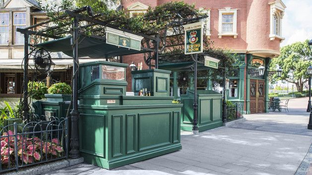 a greenery-covered beer kiosk outside rose & crown pub & dining