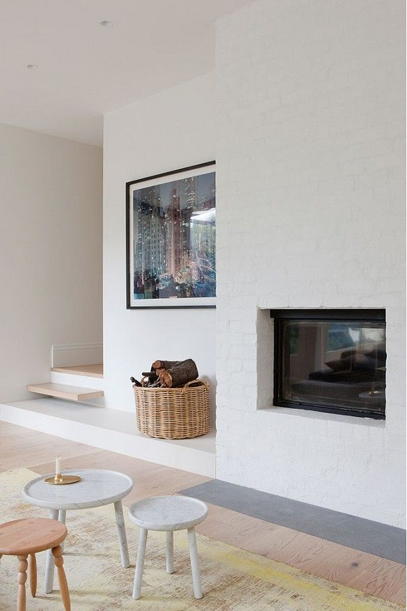 Fireplace in white living room with oversized art and wicker basket full of wood
