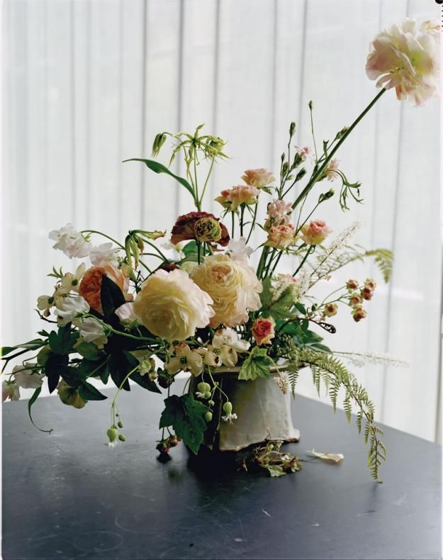 Using a cake stand from potter Joan Platt, florist Sarah Ryhanen secures a floral frog to the stand with floral putty. Gloriosa lilies, ranunculus, spray roses 'Radish' and 'Giuliano,' and long-lasting sweet pea take a star turn in this arrangement, playing nicely with dogwood branches, ghost fern, and heucherella from photographer Maria Robledo's garden.
