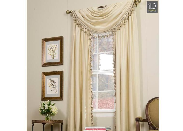 Stylish Cream Colored Curtains   Beautifully Draped Tassel Lined Curtains  Over Polished Metal Hardware Add Style