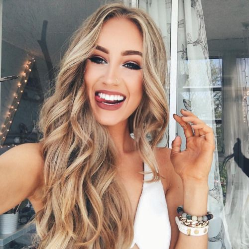 beautiful eye make up, winged eyeliner, cut crease, brown orange earthy eyeshadow, soft matte brownish reddish lipstick, contouring, nose piercing, highlight, long blonde waves, hair, hairstyle, bracelets
