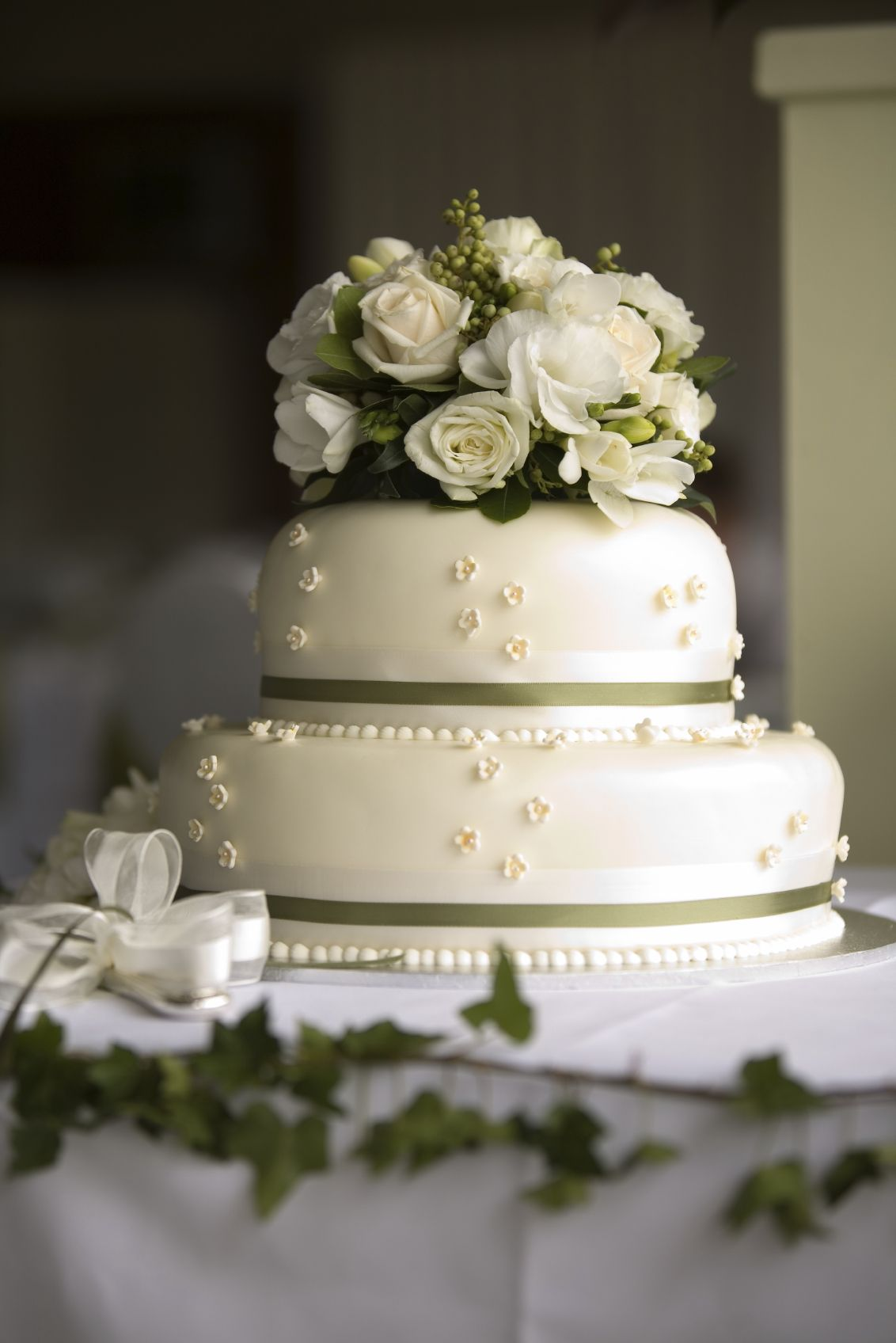 Two tier fondant covered cream wedding cake with miniature