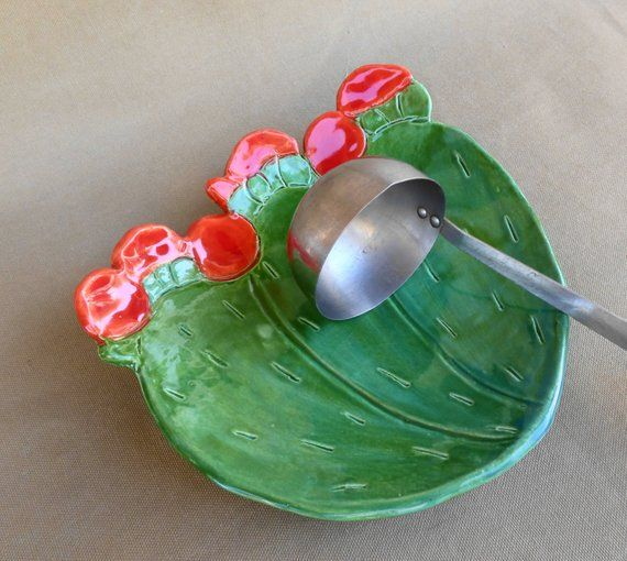 Cactus Spoon Rest, Prickly Pear Cactus dish, pottery cactus serving dish with red flowers, food safe glaze, ceramic plate, kitchen decor is part of Cactus decor Kitchen - Cactus Spoon Rest Flowering Prickly Pear cactus dish Ceramic serving plate Functional pottery art Handmade from slab clay Hand cut and glazed with multiple layers of green and turquoise  glaze  And Red glaze for the flowers Food safe glaze Kiln fired durable Great table  or kitchen decor,  Makes a nice wedding or house warming or Mother's day gift  Made in Tucson, AZ Measures 8 25  x 8