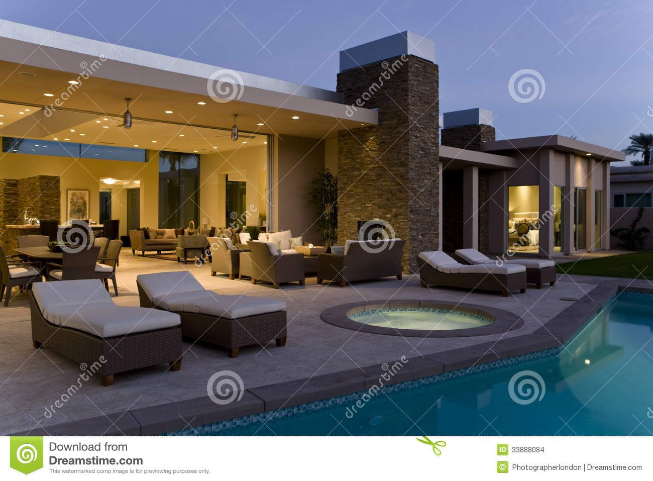 House With Sunloungers On Patio By Pool At Dusk From Over 50 Million High
