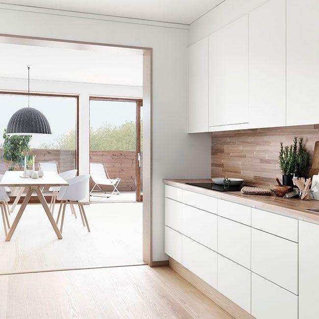 Ambiance meubles de cuisine blanc mat et plan de travail bois clair mais avec une crédence en miroir au lieu de bois superbes façades sans poignées et