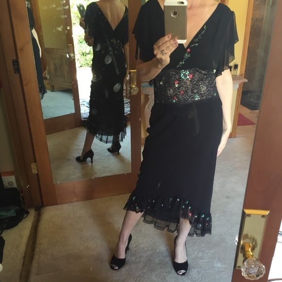 Two piece black cocktail dress This outfit looks great with boots as well. A high low hem with lace , sequins, colorful flowers at borders. The skirt has a narrow elastic waist band. This skirt will fit size 4 up to 8. The top slips over head. It says size large . However I'm a 6 on top. Very good condition. No snags , damage ,or rips. Stretch chiffon . Lapis Dresses High Low