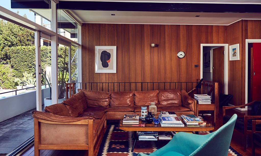 """A late '70s Danish brown leather sofa was bought to replace a white sofa, which wasn't practical with two little boys. """"This is the perfect place to sit and chat, read a book or magazine or fill it with clothes – folding!"""" Michelle says. The artwork is by Stephen Ormandy."""