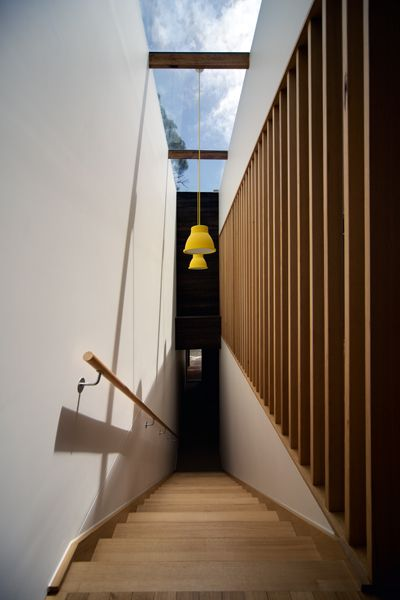 The light-filled staircase rises from the front door to the main living zones, located on the first floor. Love the hint of Yellow to direct the eye!
