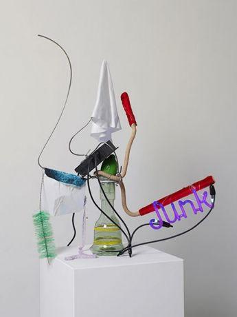"Jason Rhoades   ""Junk (Idol 36),"" 2005  Neon-glass, transformer, 240V, armature wire, print, hot glue, white fabric, glass-fruit, ribbon, hookah tube, pipe cleaner, various materials  89 x 76 x 29 cm (35 x 29 7/8 x 11 3/8 in)         Courtesy Stefan Altenburger Photography Zürich/Hauser & Wirth"