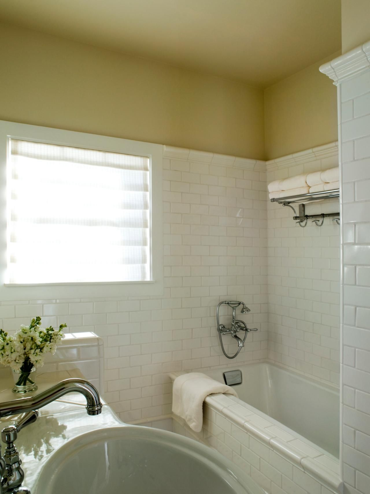 This white-tiled bathroom features a drop-in bathtub and chrome ...