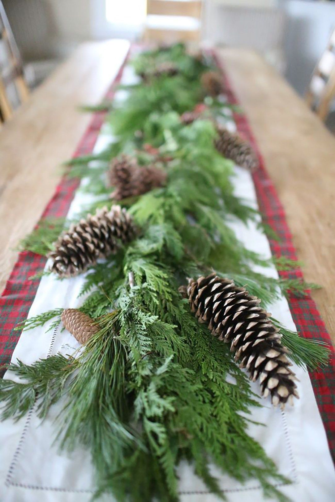 Keeping Things Simple With Pine Cones And Plenty Of Greenery Christmas Table Decorations Christmas Greenery Christmas Centerpieces