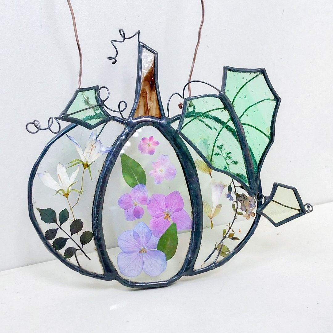 Pressed flowers and stained glass combine to make this beautiful pumpkin suncatcher, perfect for Halloween decor.