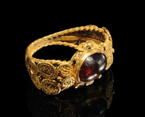 ROMAN GOLD FILIGREE RING WITH BEZEL SET CABOCHON GARNET    The filigree band composed of a double row of swirling gold roping and beads.    2nd-3rd Century AD