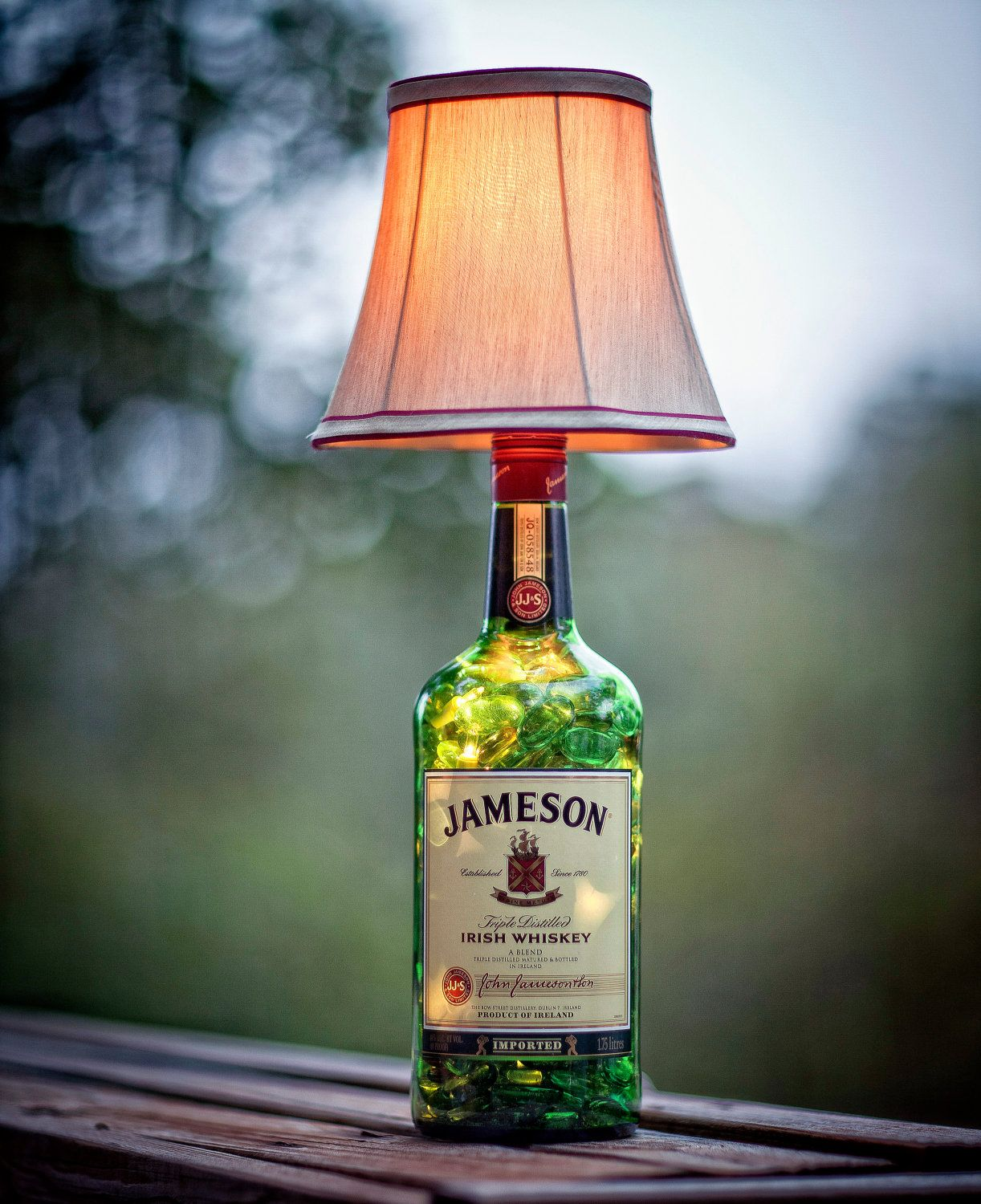 Why throw a bottle away when you can create works of art out of it . . . or a lamp