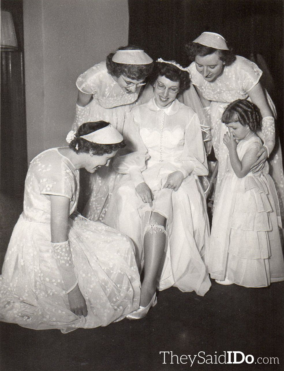 The bridesmaids look on as the bride shows off her garter. Lansing, MI 1951 {TheySaidIDo.com}