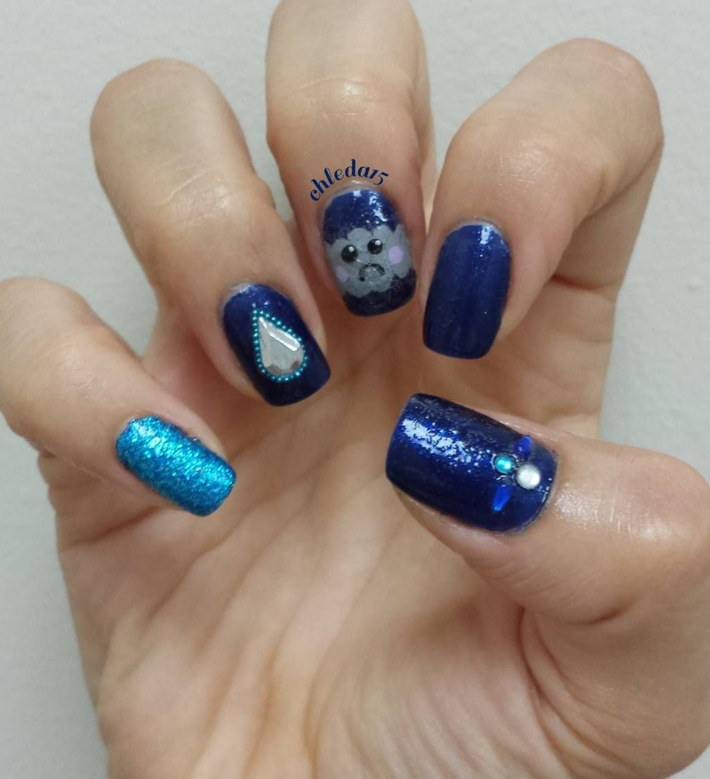 All nails are painted dark blue as base. Thumb with jewels added ...