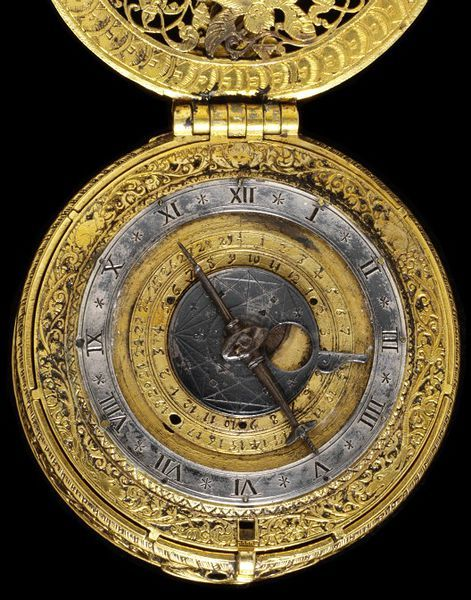 clock watch of cast and pierced engraved gilt brass with a silver dial, designed to strike the hours. Decorated back and front with engraved scenes of Abraham preparing to sacrifice Isaac, the dial showing the age of the moon, days of the month and hours. The movement is signed 'T. Chamberlin fecit'.