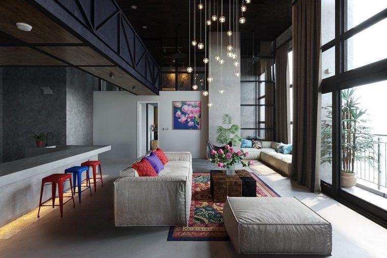 Loft con cucina e soggiorno, arredo con un divano grigio grande ...