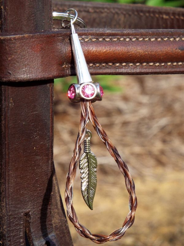 "The ""Tara"" style keychain features a 4-strand rope braid in the shape of a tear drop with a decorative bead on top and a charm dangling in the center."