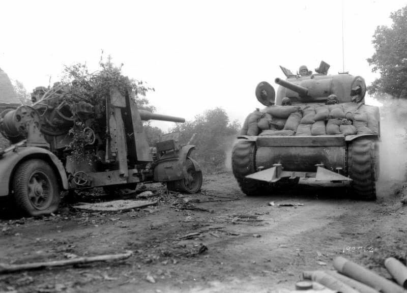 Sherman tank with hedge row cutter passing an abandoned German 88