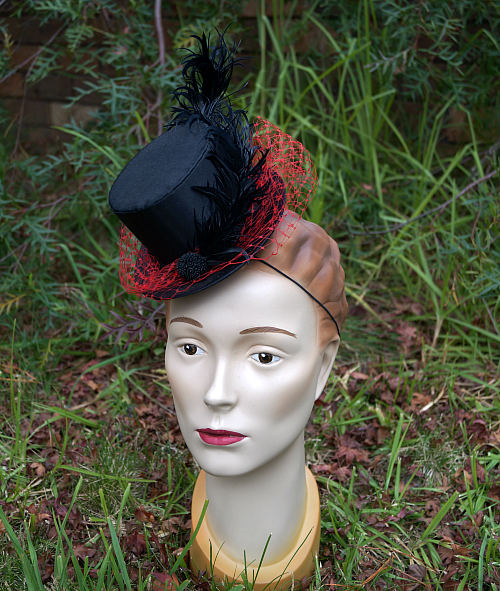 A miniature top hat in black satin with red veiling. I think I had vampire style on my mind when making it, but the black and red could suit a lot of different looks.