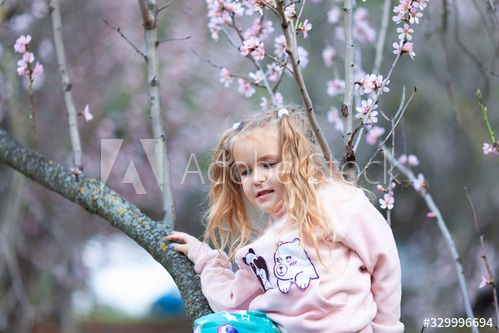 Portrait of a beautiful happy little girl on a background of blooming pink almonds #Ad , #paid, #happy, #girl, #Portrait, #beautiful, #pink