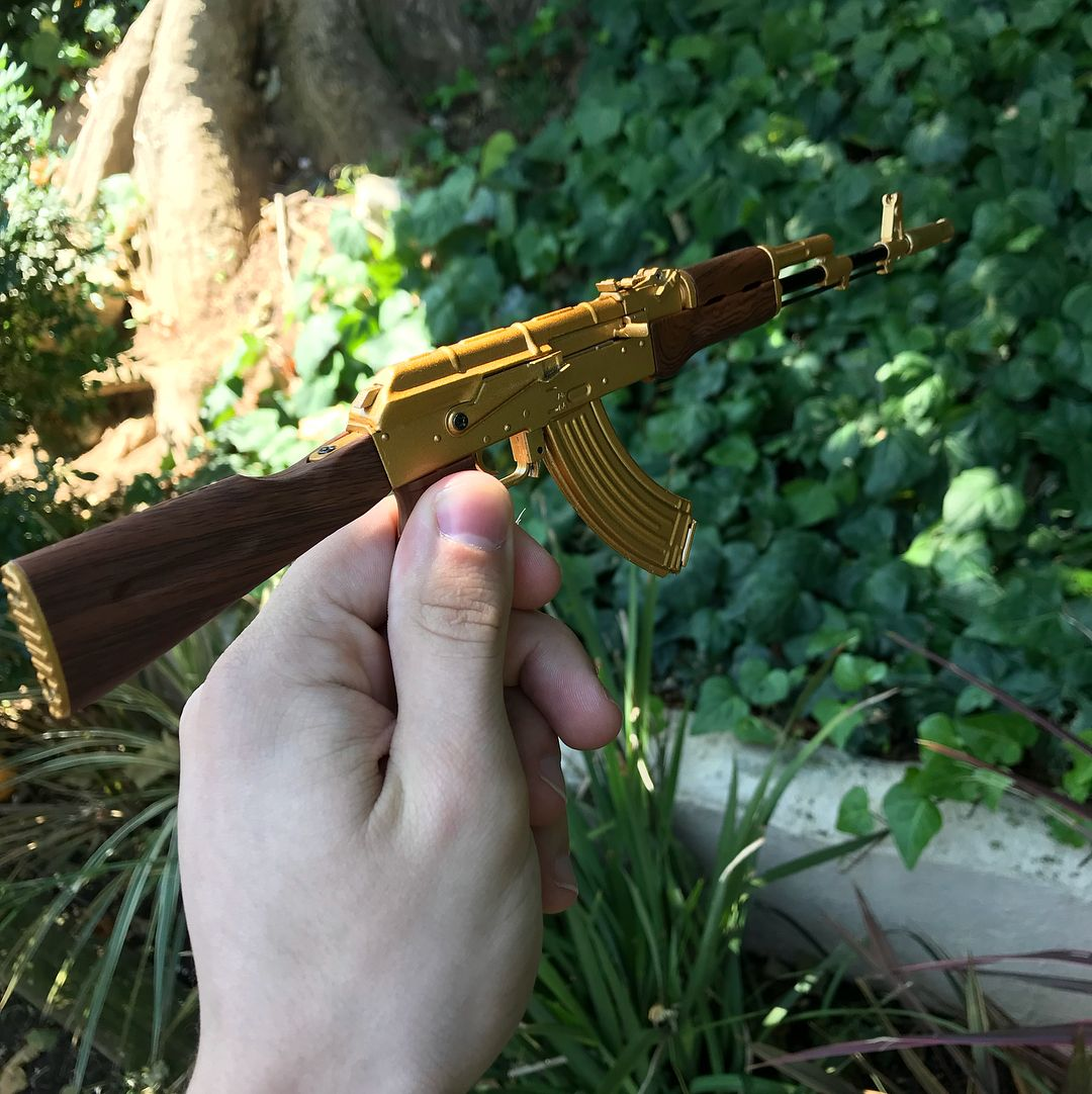 Tiny Gold AK47 being held in persons hand  All parts work and