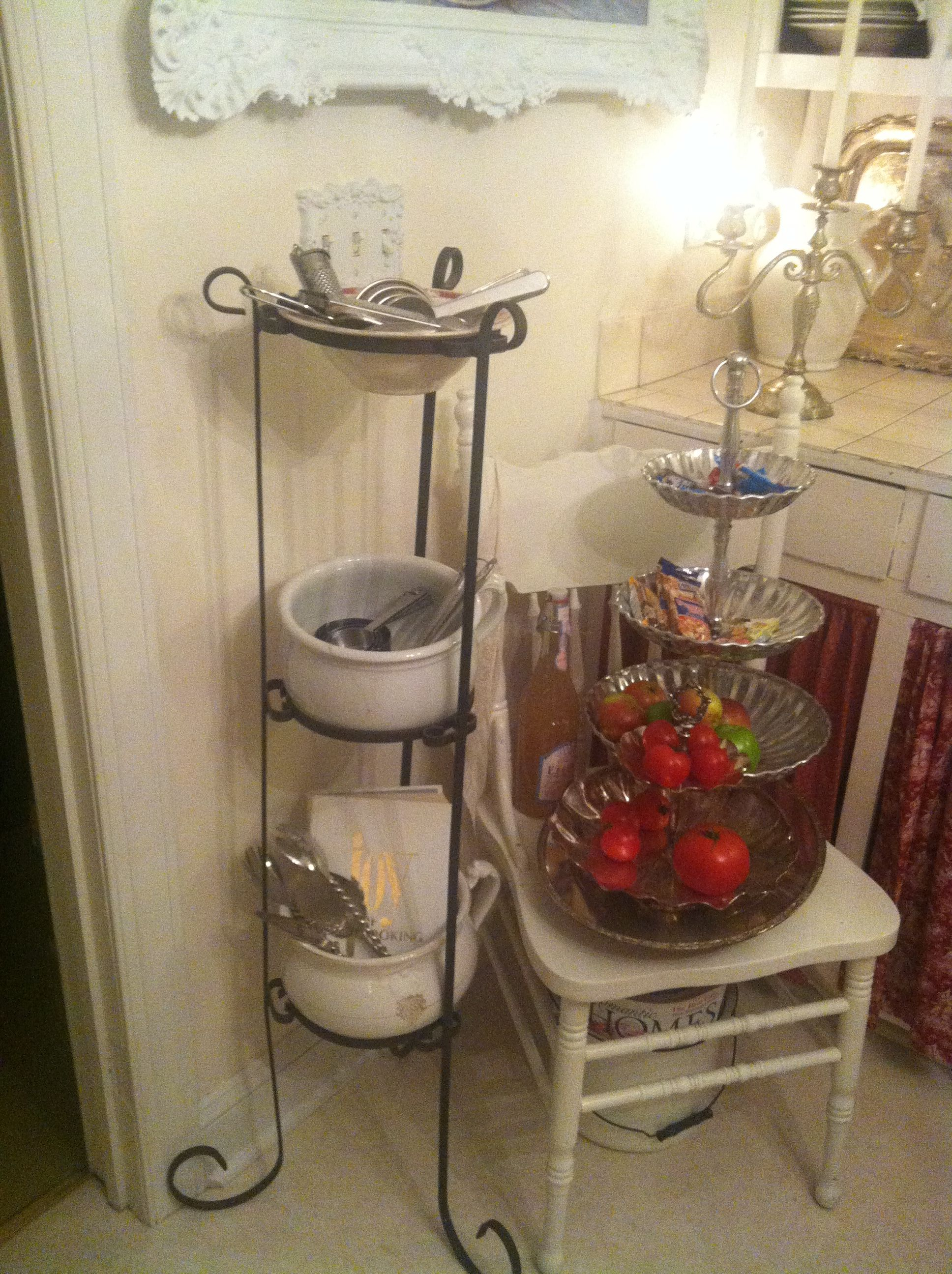 Give an old plant stand new life as a storage unit.  I used a vintage bowl on top and chamber pots for the other two.  I use it to store kitchen utensils and my collection of measuring spoons.