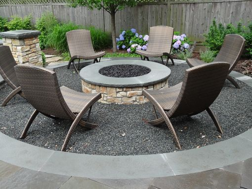 A round, masonry gas-fired fire pit clad in natural stone ...