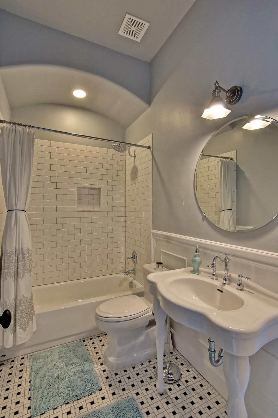 Black and white tile floors and a white tile shower create ...