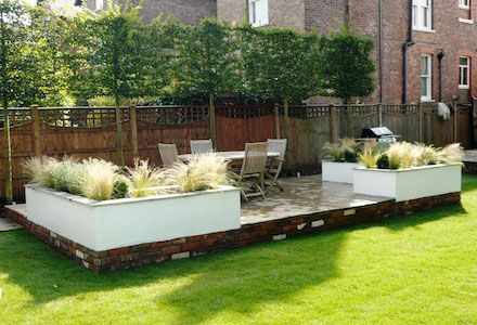 Garden Design Decking Areas raised seating decking area on bright green lawn surrounded