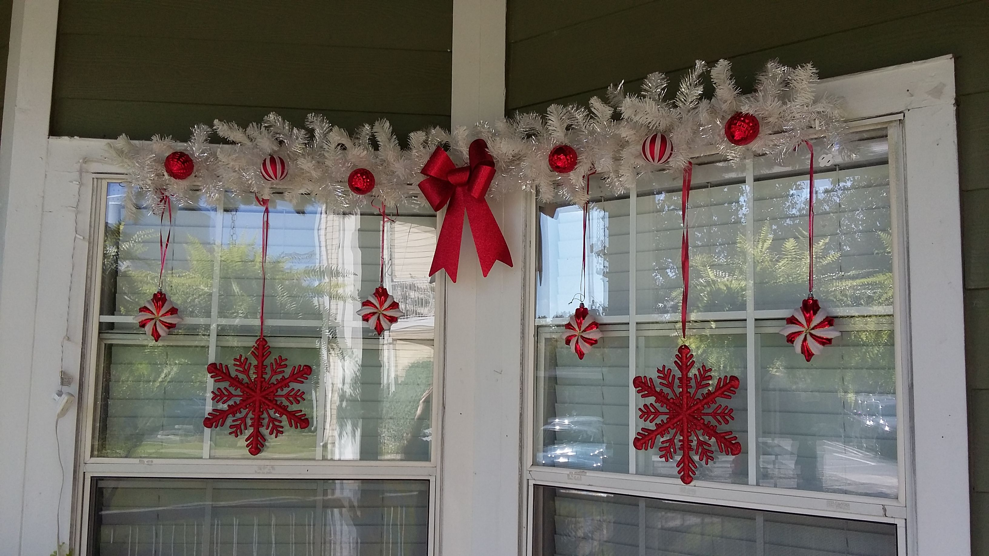 Christmas decor on my porch windows White garland red ornaments