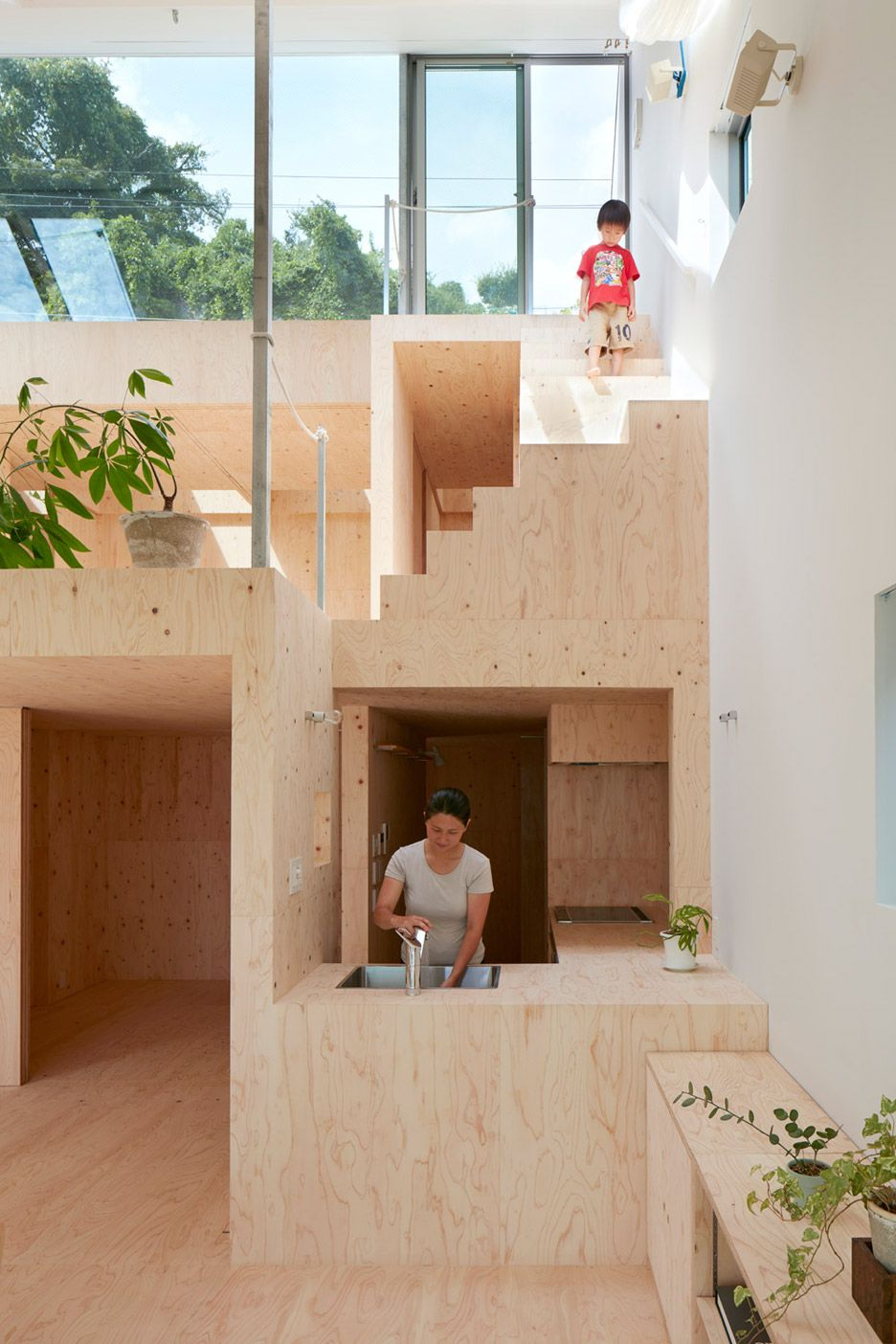 Wide Sloping Roof Shelters Plywood Filled House In Kobe By