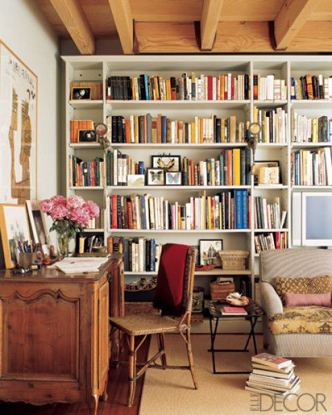 A full, multicolored bookshelf and haphazard piles of books can really warm up a space. Source: Elle Decor