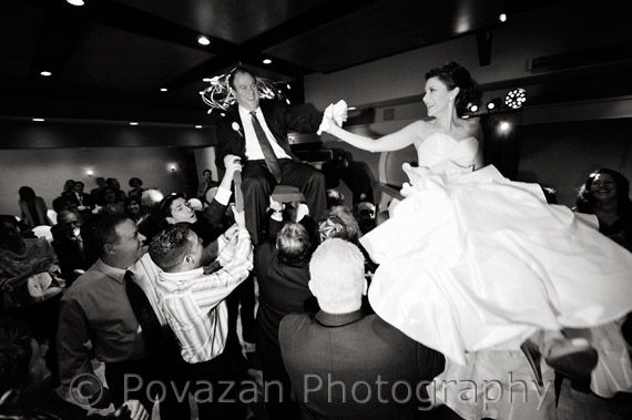 Bride And Groom Lifted On Chairs During Traditional Jewish Wedding Chair Dance