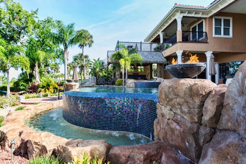 an infinity pool with a glossy glass mosaic tile waterfall that pours into small reservoir surrounded by natural stones residential pools a15 infinity