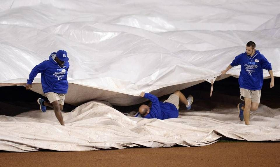 A member of the grounds crew falls under the tarp during a