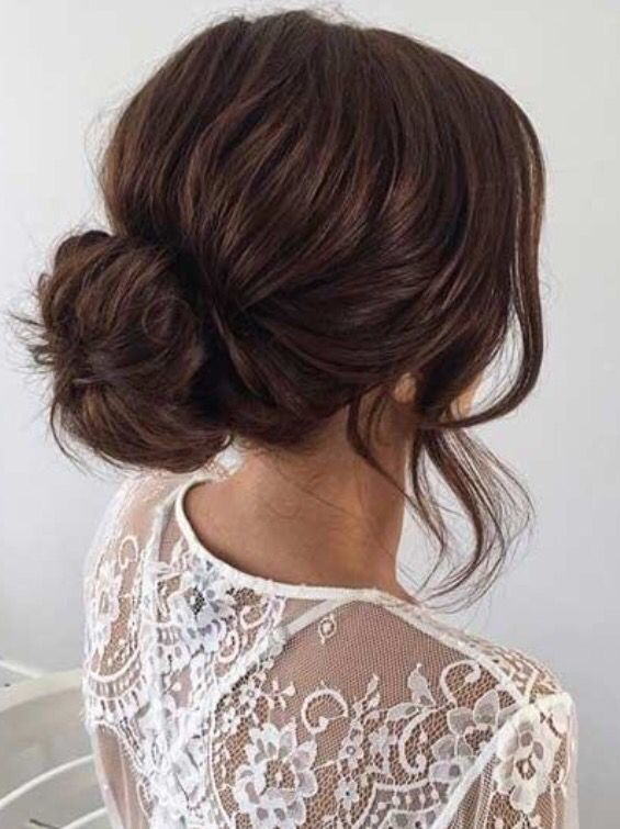 Messy bun with curled strands to frame the brides face ...