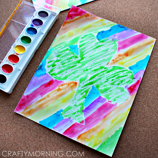 Make a pretty crayon resist st patricks day craft with your kids! It's a shamrock in the middle with rainbow stripes.