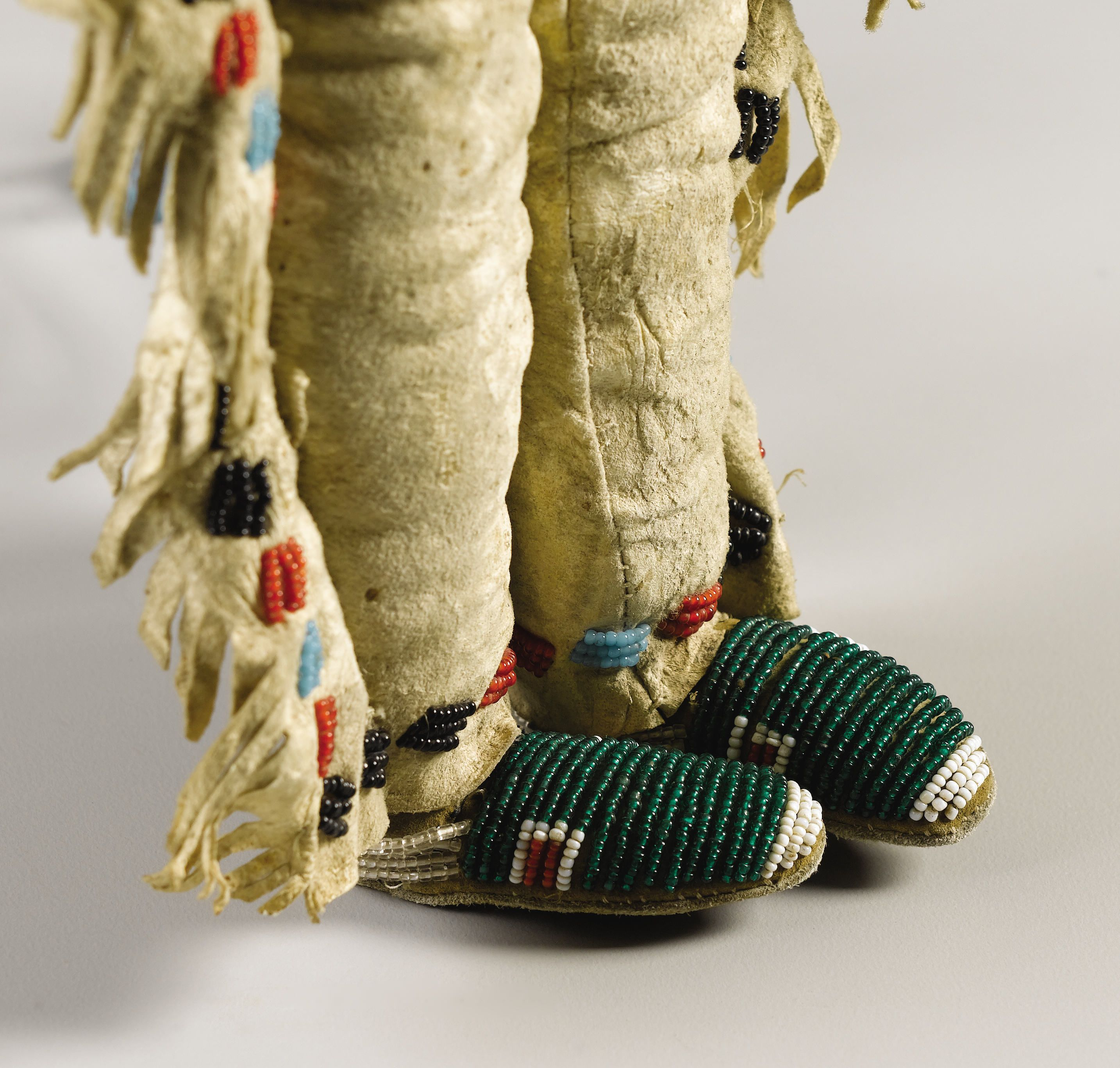 A PLAINS BEADED HIDE MALE DOLL. . c. 1890. American