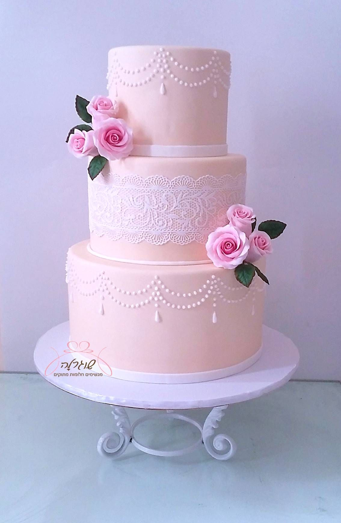 Three tiers wedding cake with lace and pearls pattern and pink roses ...
