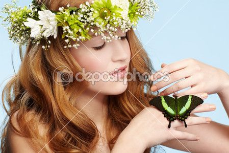 Ritratto di ragazza adolescente bella rossa sano in ghirlanda con farfalla sulla mano sull'azzurro