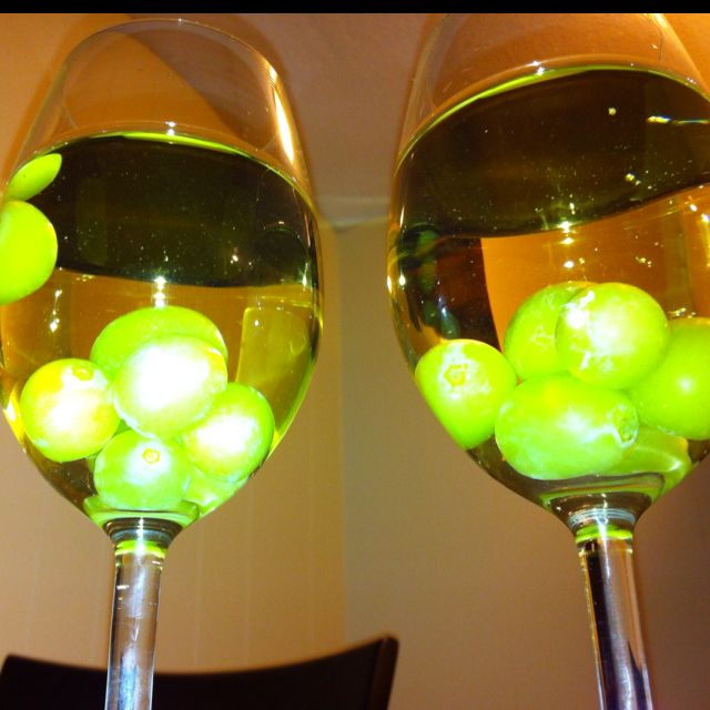 Freeze green grapes to keep white wine cold and to make a pretty presentation for guests - love this idea!!