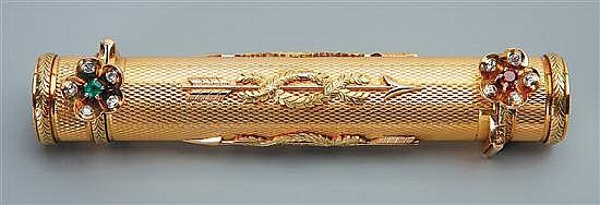 A Faberge two-colour gold double-end lipstick holder, workmaster Henry Wigstrom, St. Petersburg, circa 1910. The slender engine turned cylinder applied with arrows alternatively facing opposite directions and bound in laurel garlands, the hinged end covers with similar laurel borders with later applied diamond, ruby and emerald flower head thumbpieces.