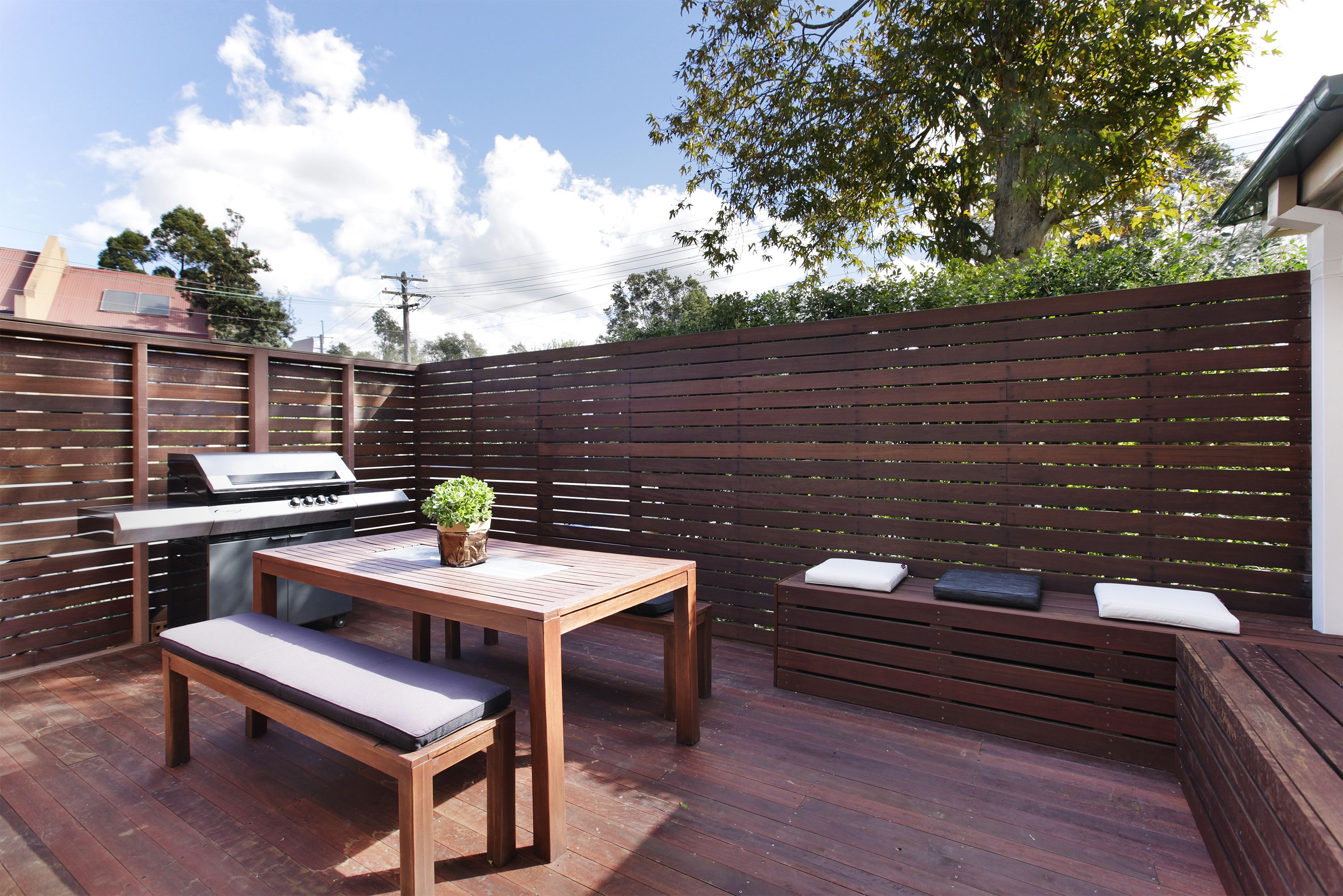 this private outdoor dining area uses timber walls and built in