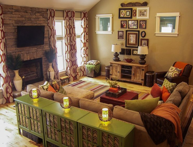 A Warm Living Room Featuring Green And Orange Earth Tones Patterned Curtains Rustic Wood And A