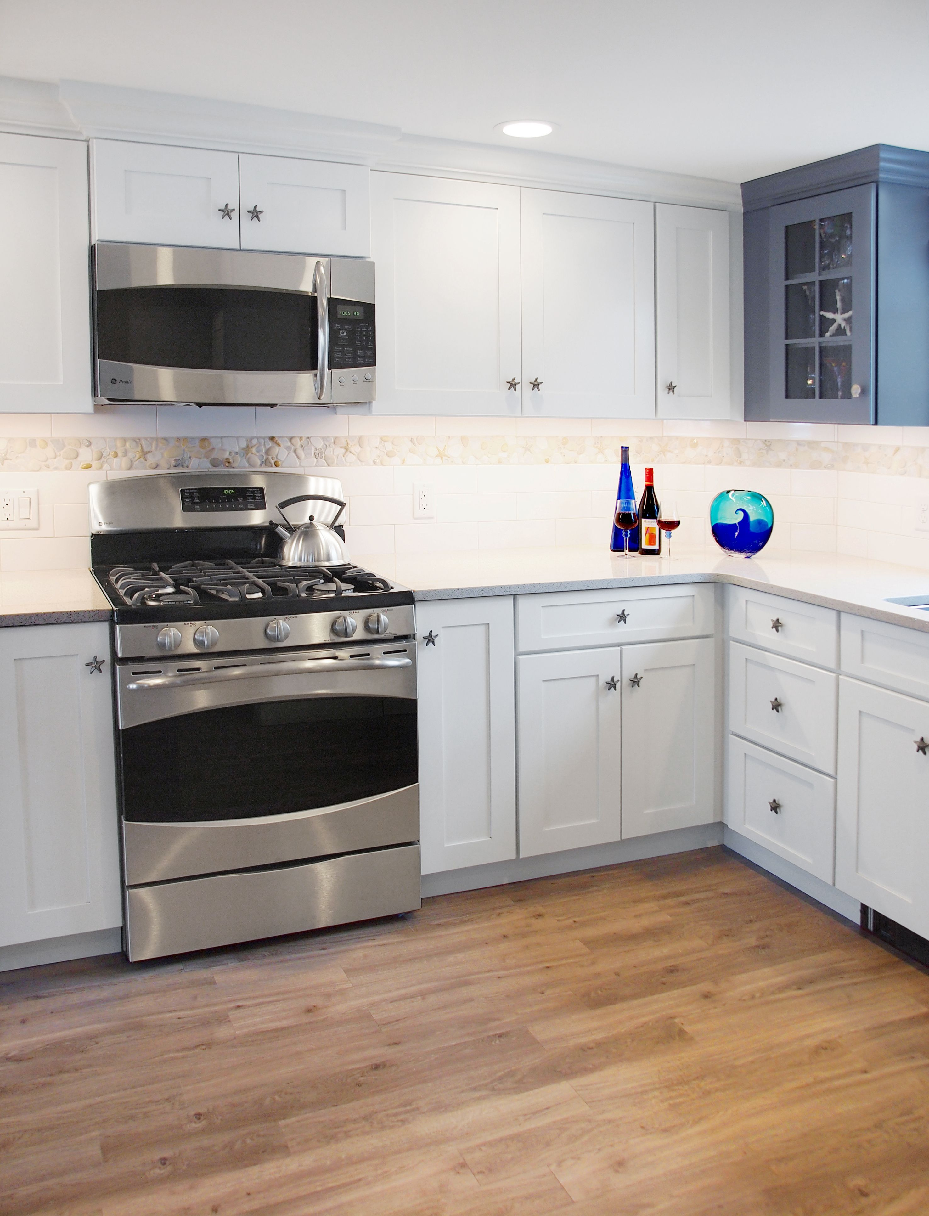 Beach house kitchen remodel by Renovisions with blue and white